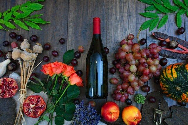 Fľaša vína medzi ovocím a kvetmi