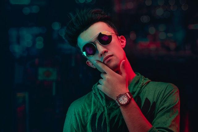 Mladý muž v zelenej košeli a slnečných okuliaroch.jpg