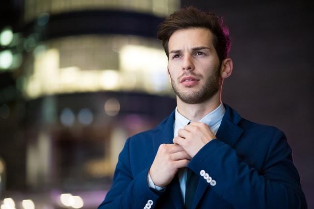 Muž v modrom obleku a v bielej košeli pozerá do diaľky