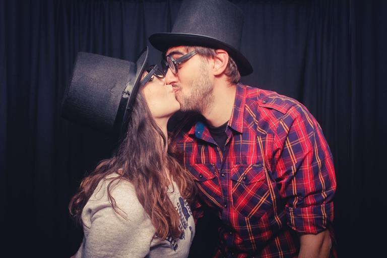Muž v červenej károvanej košeli a klobúku bozkáva ženu v sivej bunde
