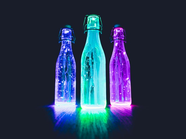 Tri svietiace fľaše v tme.jpg