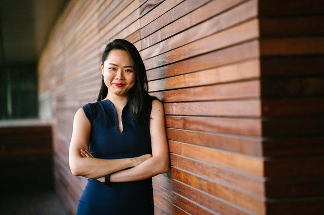 Usmiata ázijská žena opretá o drevenú stenu.jpg