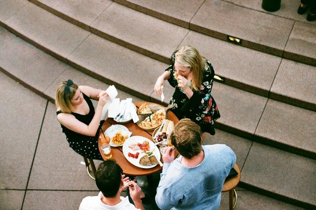 Tri ženy sedia pri stole a obedujú.jpg