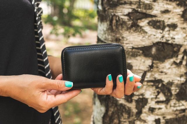 Žena a tyrkysovými nechtami otvára čiernu koženú peňaženku